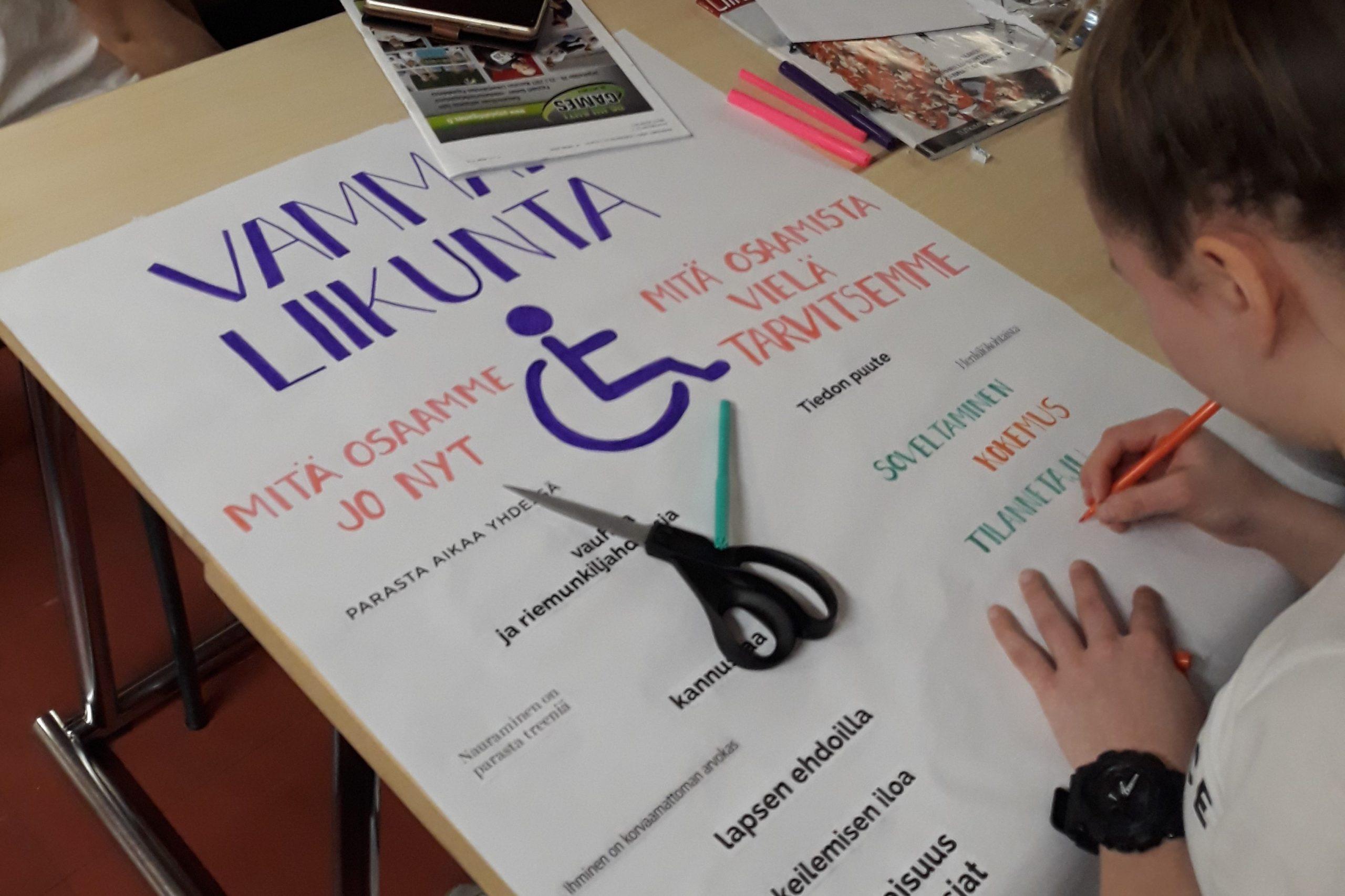 Opiskelija kirjoittaa posteriin tekstiä kompetenssityöpajassa.