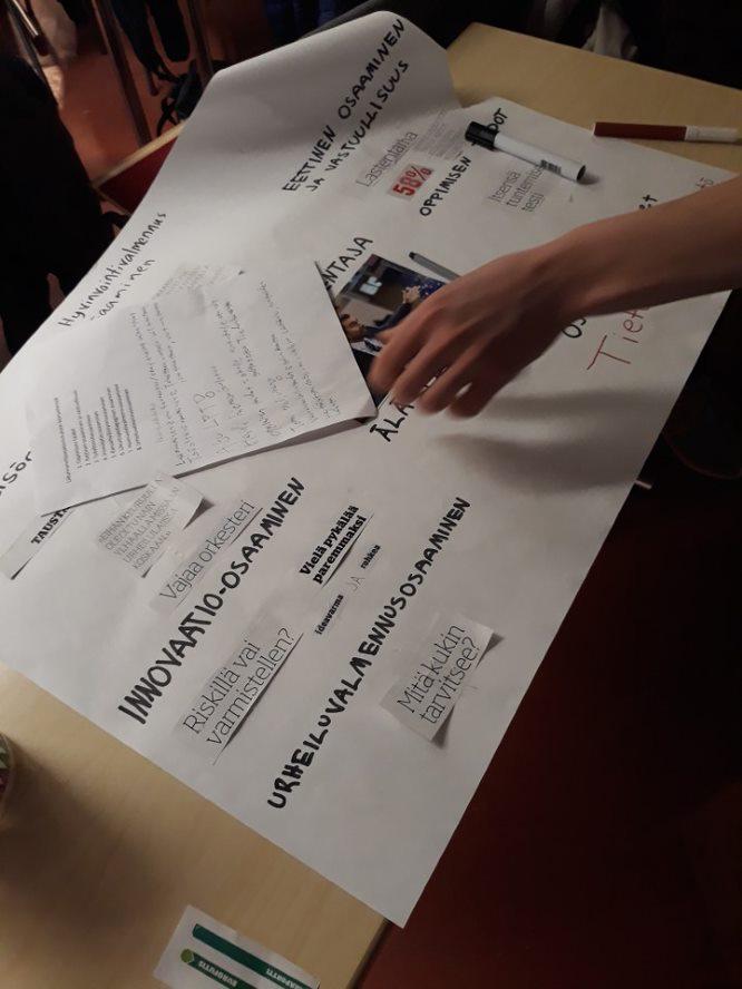 Opiskelijat tekevät kompetenssityöpajassa posteria ammatillisista kompetensseista kirjoittamalla ja liimaamalla lehtileikkeitä.