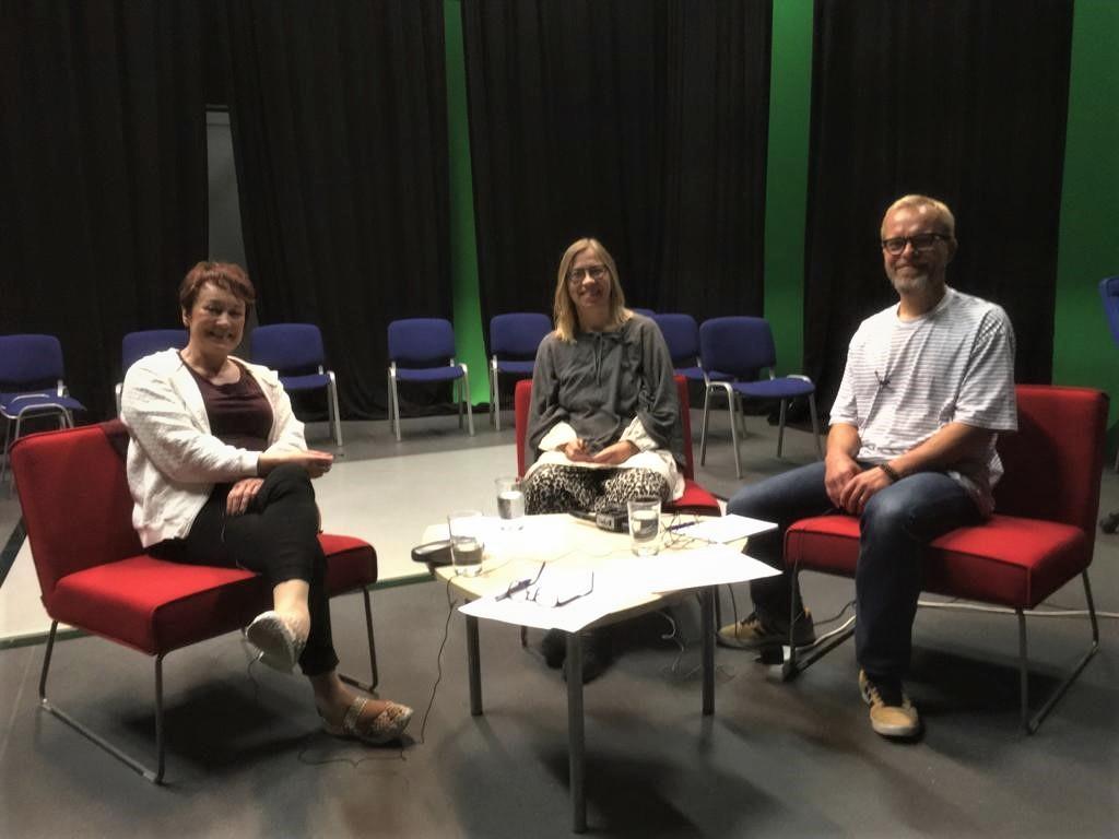 Johanna Ilola, Jaana Liukkonen ja Jussi Kareinen istuvat pöydän ympärillä podcastin nauhoituksessa.