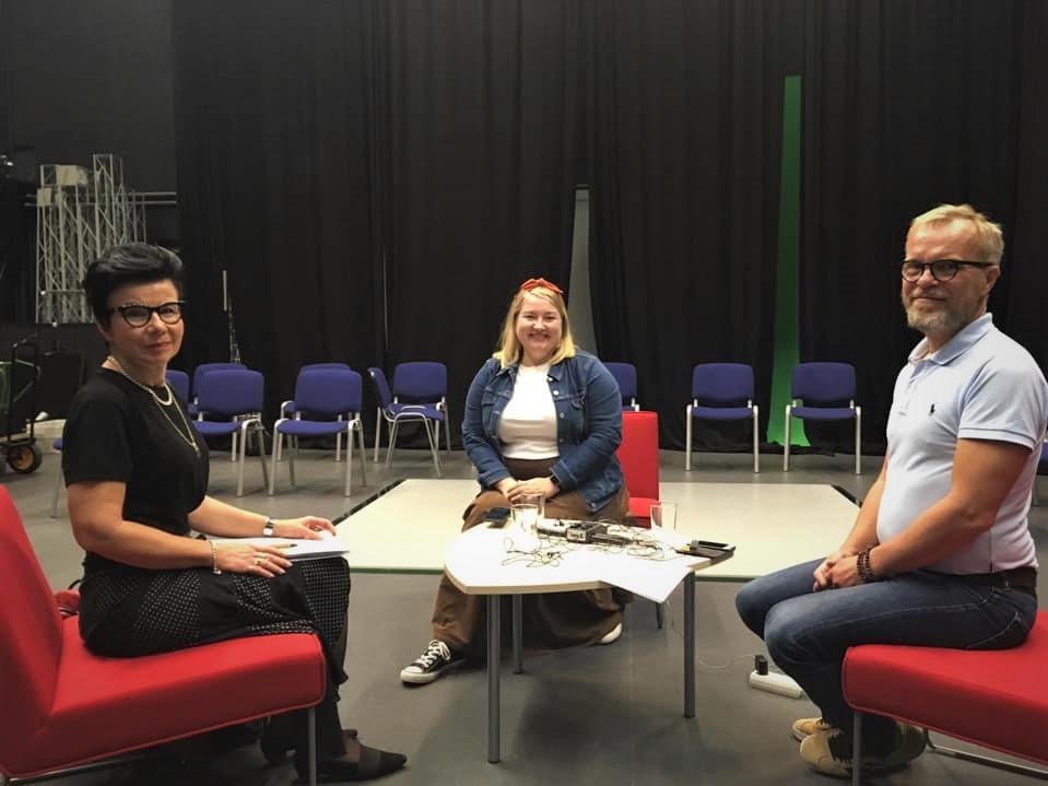 Podcastissa keskustelevat Marjo Kamila, Elsa Heiko ja Jussi Kareinen istuvat pöydän ympärillä podcastin nauhoituksessa.